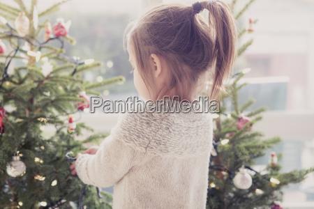 muchacha que adorna el arbol de