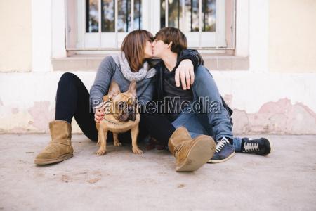 joven pareja con bulldog frances sentado