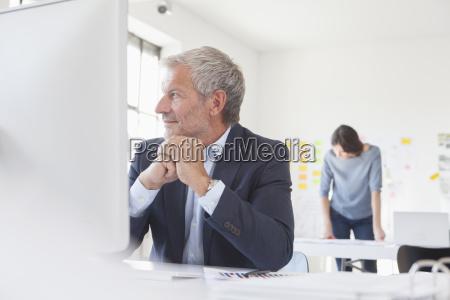 smiling businessman in office at desk