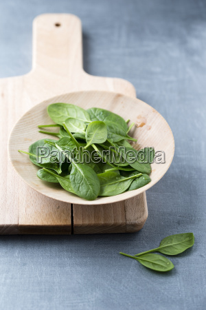 wooden bowl of spinach leaves on