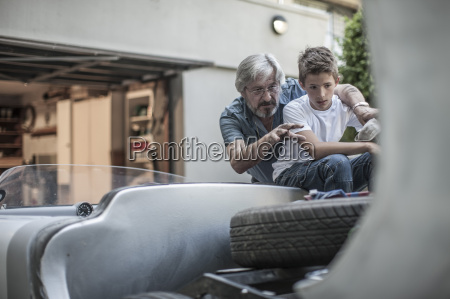 grandfather and grandson restoring a car