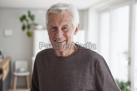 portraet af smilende senior mand derhjemme
