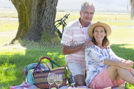 senior couple sitting on picnic blanket