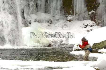 a young woman fly fishes on