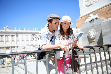 pareja leyendo libro de viajero por