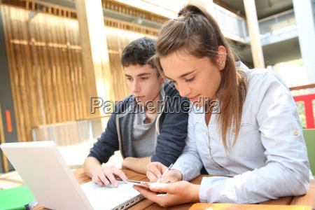 adolescentes trabajando en laptop en el