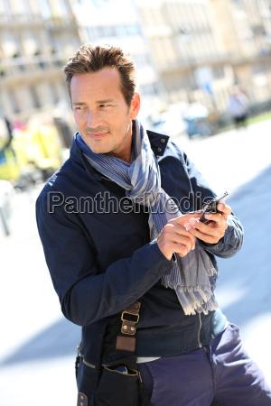 trendy man in town using smartphone