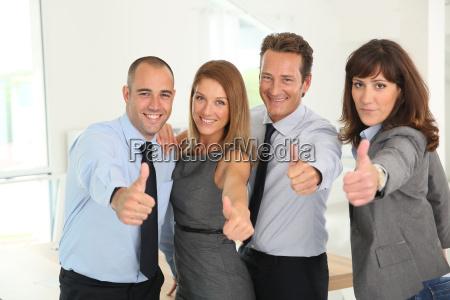 equipo de negocios exitoso mostrando pulgares
