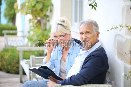 pareja mayor leyendo libro fuera de