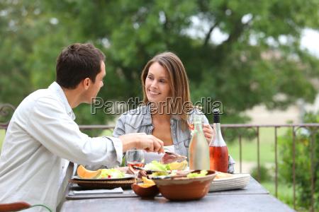 pareja alegre almorzando en el jardin
