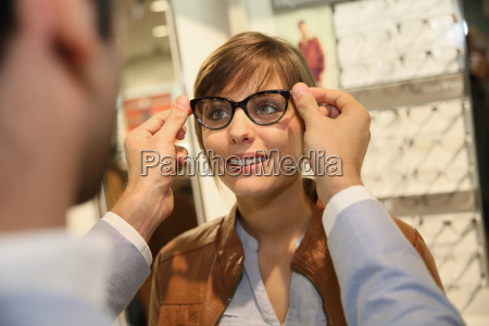 young woman with optician in optical