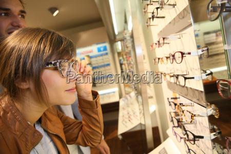 young woman in optical shop trying