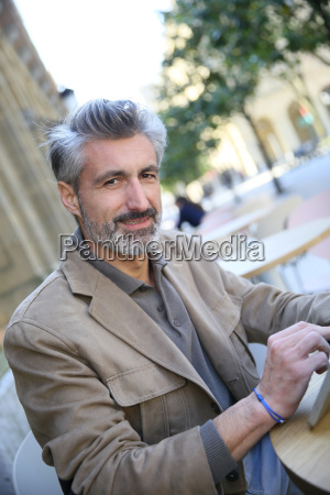 mature man in town using tablet