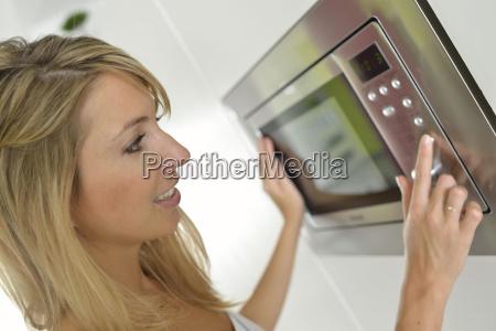 mujer en casa con horno microondas