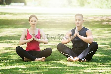 pareja joven practicando yoga