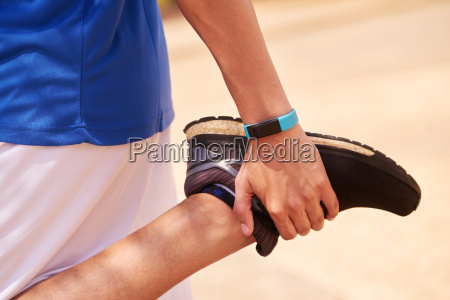 young man sports stretching using fitwatch