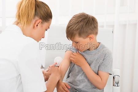 doctor dando una inyeccion al ninyo