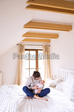 father with baby sitting on bed