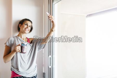 mujer sonriente joven con bebida saludable
