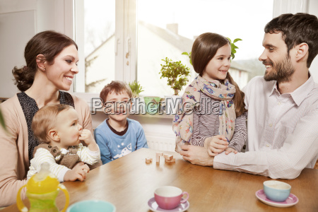 happy family of five sitting at