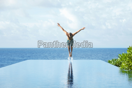 young man diving in pool