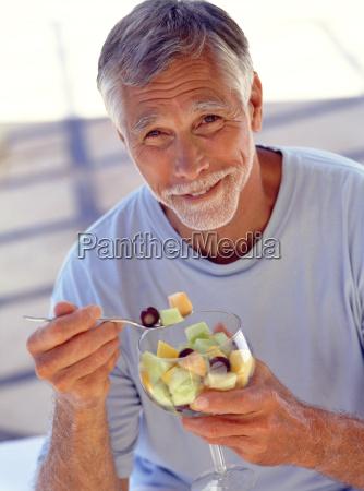 retrato de hombre maduro comiendo coctel