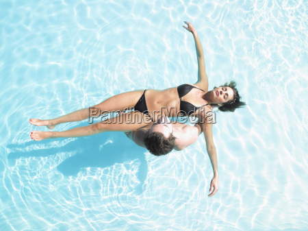 man holding woman floating in pool