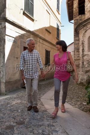 older couple walking on cobbled street