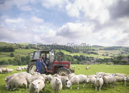 granjero en tractor con hijo observando
