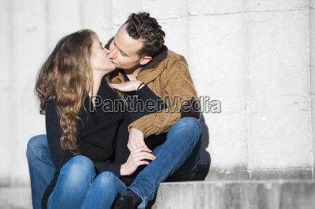 romantica pareja besandose mientras esta sentado