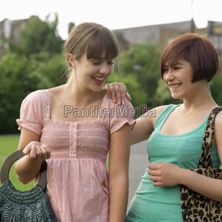2 young woman laughing with bags