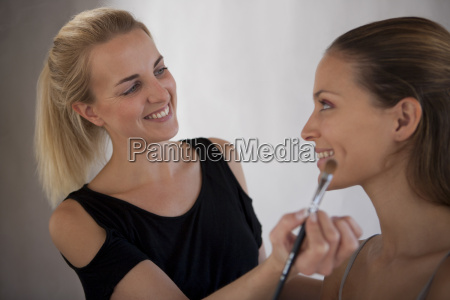 makeup artist applying makeup to model
