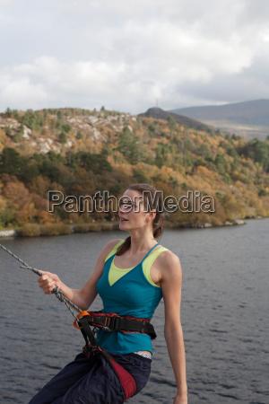 woman climbing a rock face