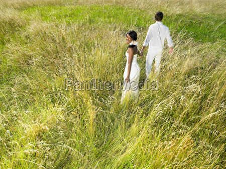 married couple walking in a field