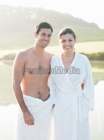 couple in towels by lake
