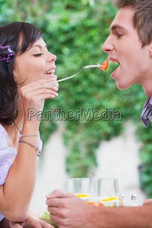 woman feeding man piece of tomato