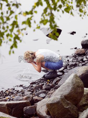 woman washing face in lake