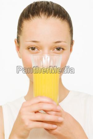 girl holding a glass of orange