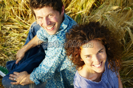 couple sitting in a wheat field