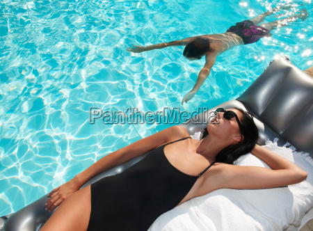 woman tanning by the pool man
