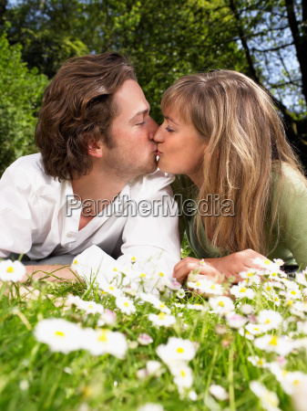 couple lying in the grass kissing