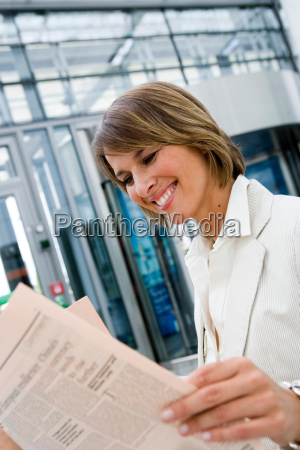 woman reading newspaper smiling