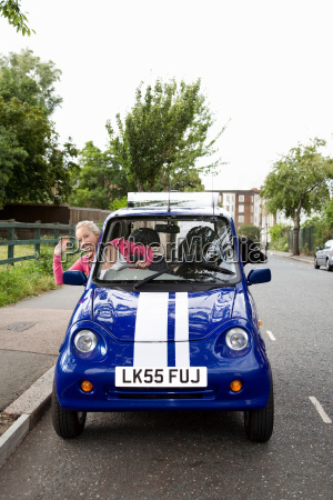 young woman waving from electric car