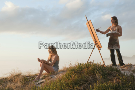 young man painting with young woman