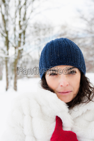woman in snowy woods looking to