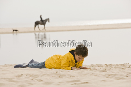 young boy lying on sand at