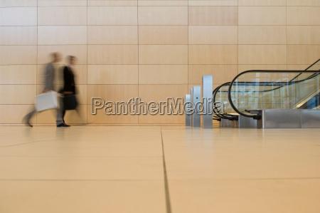 business people walking towards an escalator