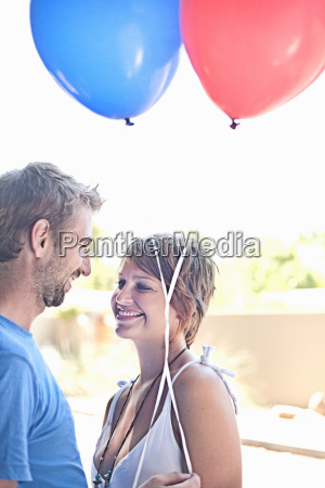 couple with balloons smiling outdoors
