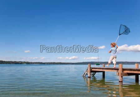 boy fishing with net in lake