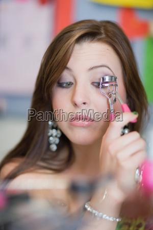 teenage girl applying makeup